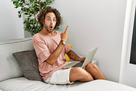Young hispanic man sitting on the sofa at home using laptop surprised pointing with finger to the side, open mouth amazed expression.