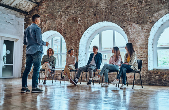 Confident male leader, coach talking with group of office workers, having good conversation with subordinate, brainstorming, discussing business strategy, ideas, team building activity.