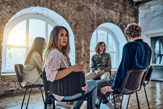 Portrait of young female professional psychologist or counselor looking at camera with people on background.
