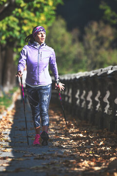 Nordic walking on sidewalk. A young woman practices