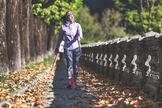 Nordic walking on sidewalk. A young woman practices_2