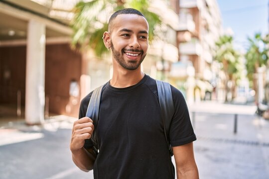 Young african american man smiling confident wearing backpack at street
