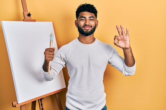 Arab man with beard standing by painter easel stand holding brushes doing ok sign with fingers, smiling friendly gesturing excellent symbol