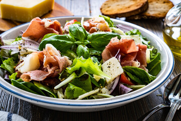 Obraz Tasty salad - prosciutto di Parma, parmesan and fresh, green vegetables on wooden table  - fototapety do salonu