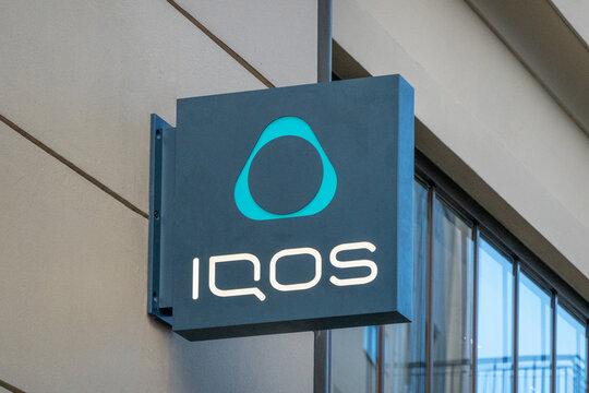 Vilnius, Lithuania - October 16, 2021: IQOS store signboard in Vilnius, Lithuania. IQOS is tobacco heating system, HeatStick brand
