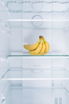 against the background of a white refrigerator, on a glass shelf, there are bananas