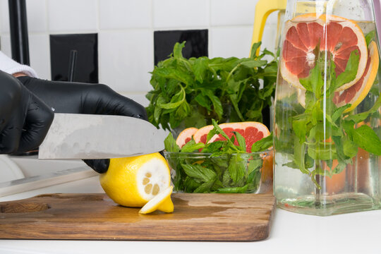 the process of cooking lemonade by the chef, hands in black gloves, cut with a sharp knife, lemon, against the background of the finished drink in a jug