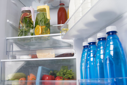in an open white refrigerator, we have shelves, soft drinks, citrus lemonade in a jug, bottled water, food and vegetables
