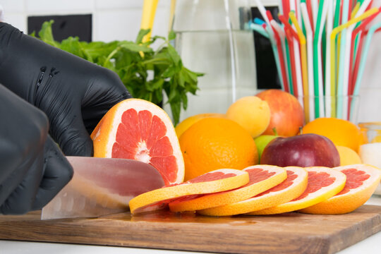 close-up, the bartender's hands are cutting grapefruit slices with a knife to make a cocktail