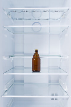 a bottle of beer in the refrigerator on a glass shelf, on a white background