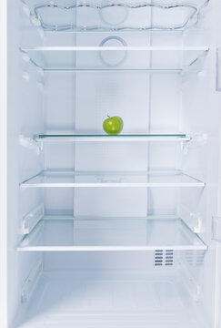against the background of a white refrigerator, on a glass shelf, there is a green apple