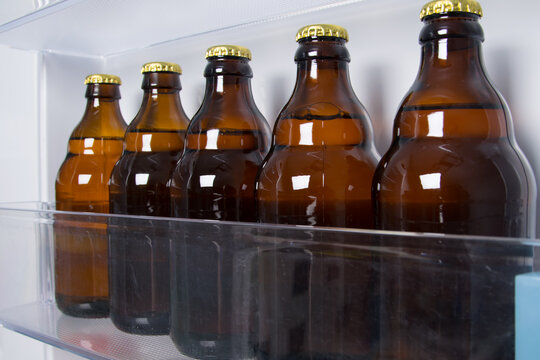 against the background of an open white refrigerator, glass bottles with beer are on the shelf, close-up