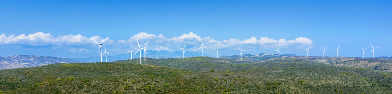 Oreites wind farm in Cyprus, wide panorama, landscape with green hills and blue sky