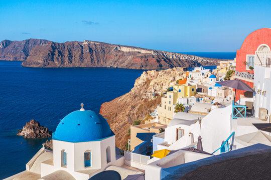 Oia village with famous white houses and blue churches on Santorini island, Aegean sea, Greece.