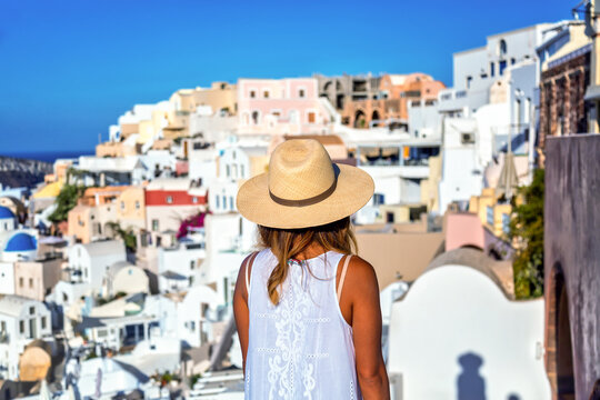Beautiful tourist girl in straw hat against Oia village with famous white houses and blue churches on Santorini island, Aegean sea, Greece. Travel concept