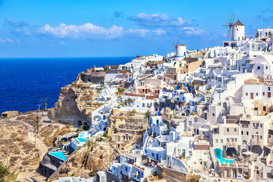 Greece vacation iconic background. Famous Oia village with traditional white houses and windmills during summer sunny day Santorini island, Greece.