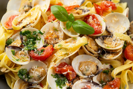 White shell clams in Garlic and parsley white wine sauce tagliatelle pasta served with cherry tomatoes and parmesan cheese