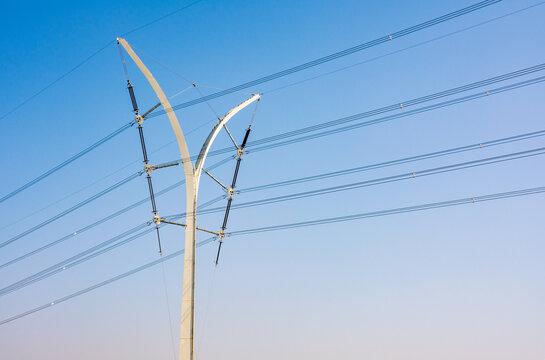 Futuristic Electricity Pole against blue Sky