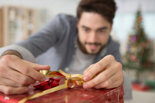 man securing ribbon around a christmas present