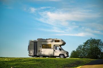 Obraz Closeup shot of a camper van parked in the green field under the blue sky - fototapety do salonu