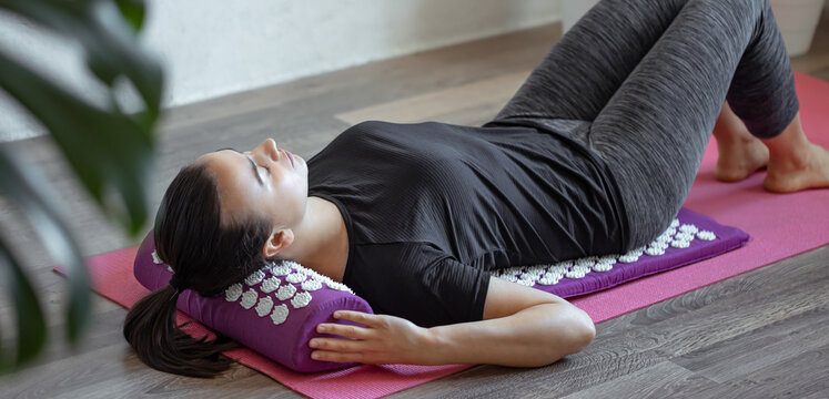 Young woman on acupressure mat in home acupuncture massage.