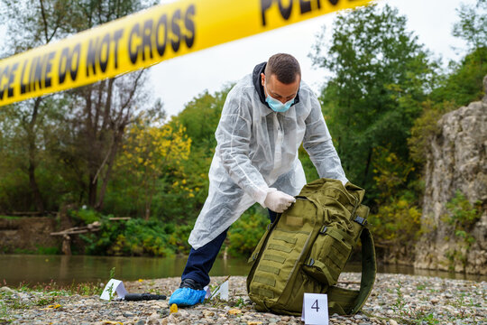 Forensic police investigator collecting evidence at the crime scene by the river in nature