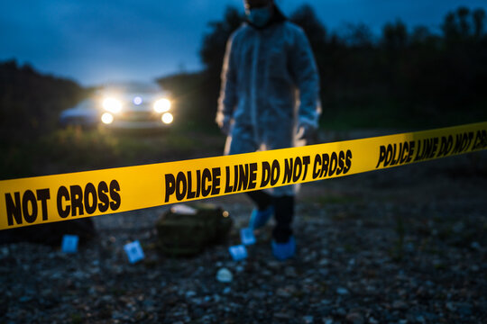 Forensic police investigator collecting evidence at the crime scene by the river in nature at night selective focus on police line tape
