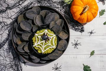 Obraz Spooky Halloween black potato chips with guacamole dip - fototapety do salonu