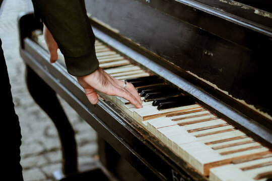 The man plays the piano. Lifestyle. Musical instrument on the street. Hand and piano keys close up. Creative life.