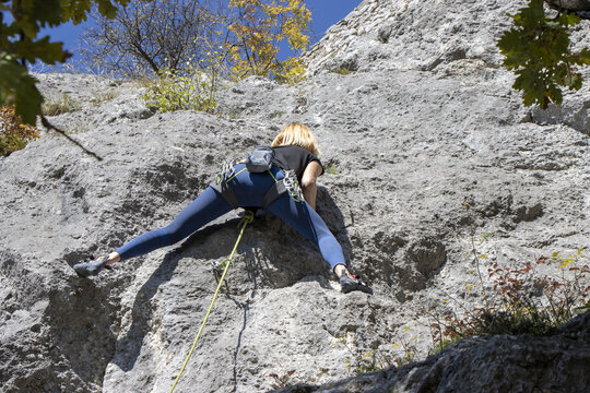 Young woman climbing natural high rocky wall