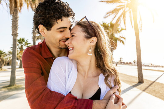 Beautiful romantic couple embracing outdoors - Hipster young man hugging in love his girlfriend in the morning at the beach - Love relationship and honeymoon concept