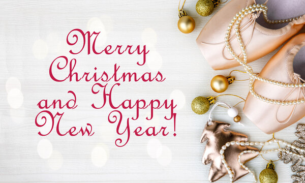 Merry Christmas and Happy New Year text. Pair of pink Pointe Shoes, christmas tree, golden balls, gold star, pearl beads on white wooden background. Christmas concept, top view, card, monochrome