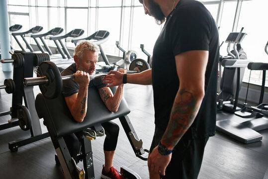 Coach with elder client in gym