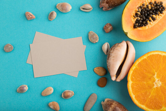 Gray paper business card with ripe cut papaya, orange, seashells on blue pastel pastel background. Top view, copy space, close up.