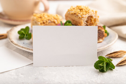 White paper business card and set of eclair on gray concrete background. side view side view, close up.