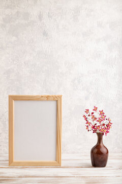 Wooden frame with purple barrenwort flowers in ceramic vase on gray concrete background. side view, copy space, mockup.