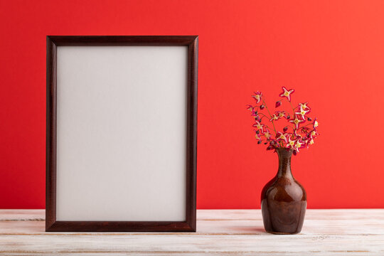 Wooden frame with purple barrenwort flowers in ceramic vase on red pastel background. side view, copy space, mockup.