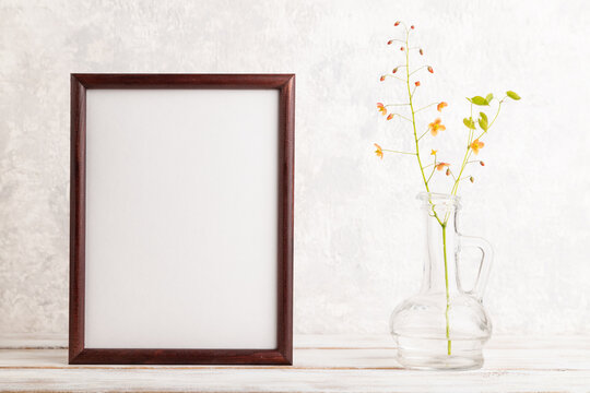 Wooden frame with orange barrenwort flowers in glass on gray concrete background. side view, copy space, mockup.