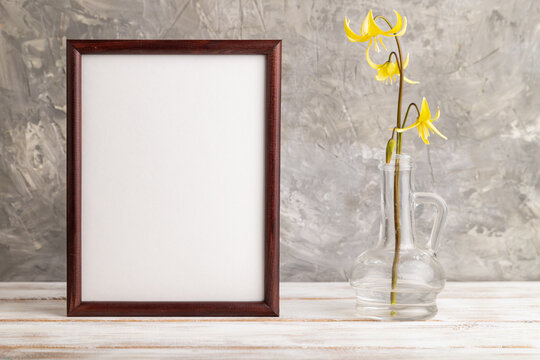 Wooden frame with yellow trout lily or dogtooth violet flowers in glass on gray concrete background. side view, copy space, mockup.