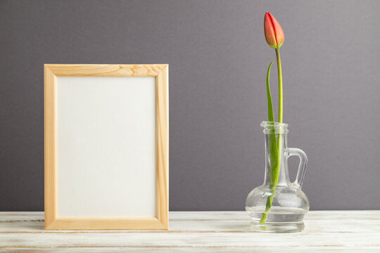 Wooden frame with red tulip flower in glass on gray pastel background. side view, copy space, mockup.