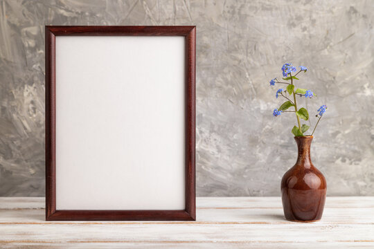 Wooden frame with blue forget-me-not flowers in ceramic vase on gray concrete background. side view, copy space, mockup.