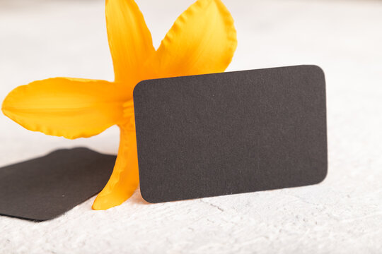 Black paper business card mockup with orange day-lily flower on gray concrete background. side view, copy space.