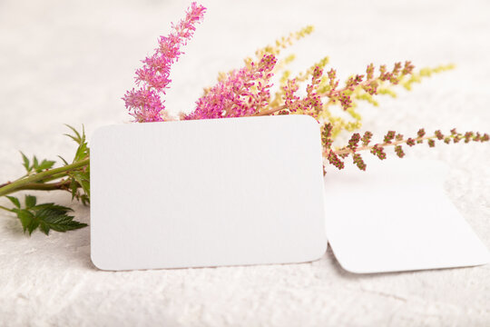 White paper business card mockup with purple astilbe flowers on gray concrete background. side view, copy space.