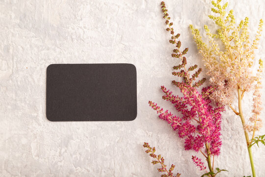 Black paper business card mockup with purple astilbe flowers on gray concrete background. top view, copy space.