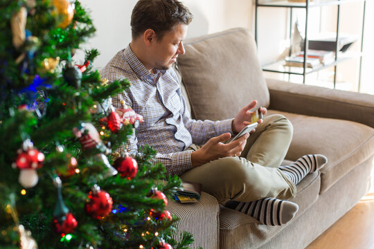 Man buying Christmas, New Year gifts online using phone, laptop
