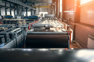 Obraz Industrial factory workshop or warehouse interior inside for metal roof tiles production. Production of roofing on automated conveyor belts and lines equipment. - fototapety do salonu