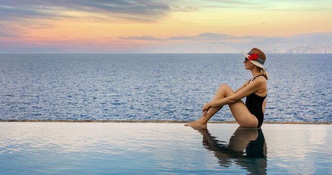 woman relaxing on the edge of infinity swimming pool at luxury resort. summer vacation. banner copy space