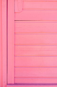 Weathered wooden plank painted in pink color