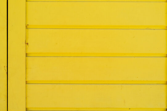 Weathered wooden plank painted in yellow color