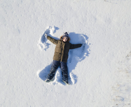 Happy boy play on snow and making snow angel figure with hands and legs